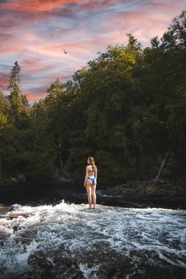 Girl in blue 2 piece bathing suit on a river rapid