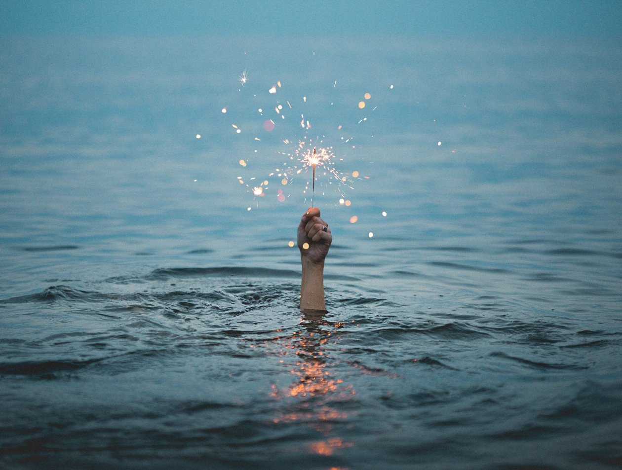 person submerged on body of water holding sparkler - geothermal heat